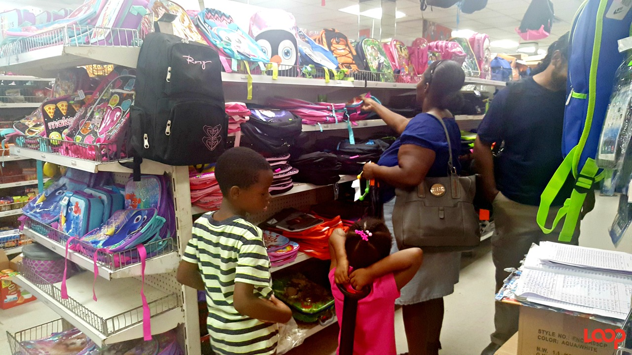 Mother and kids shopping for school bags in F.W. Woolworth Barbados.