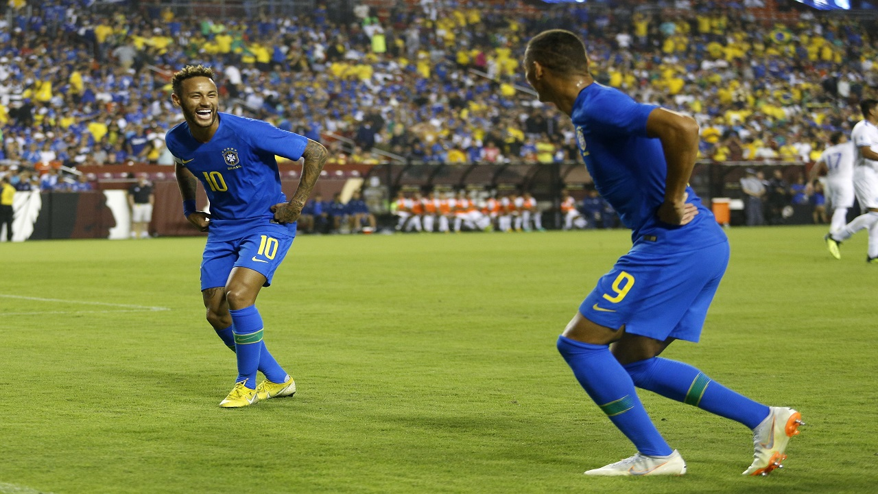 Brazil forward Neymar, left, celebrates with teammate Richarlison after Richarlison scored a goal in the first half of a football match against El Salvador, Tuesday, Sept. 11, 2018, in Landover, Md.