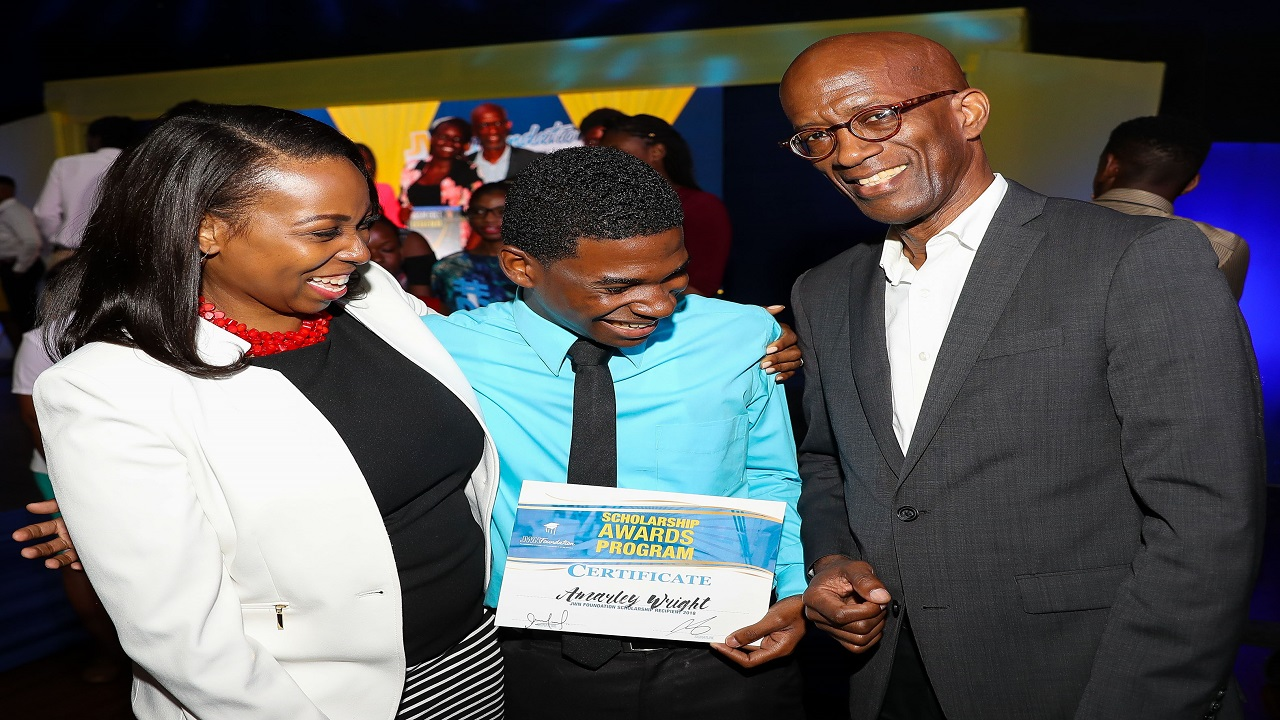 Clement Lawrence (right), Chairman, JWN & JWN Foundation and Odetta Rockhead-Kerr (left), Vice President and Country Manager, Sutherland Global, embrace recipient Amarley Wright during the 2018 JWN Foundation Scholarship Awards ceremony.