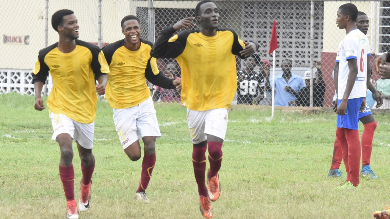 Nickashe Murray (centre) of Wolmer's Boys' School celebrates his goal against Holy Trinity on Monday. Wolmer's won the game 2 - 1. (PHOTOS: Marlon Reid)