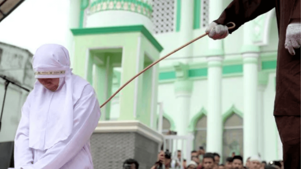 A 20-year-old Muslim woman gets caned after being caught in proximity to her boyfriend in Banda Aceh, Indonesia. Picture: AFP / Chaideer MahyuddinSource:AFP