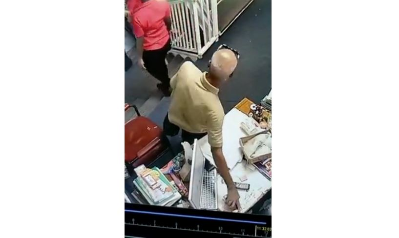 This still from surveillance footage shows the suspect grabbing a cell phone left on a table at a San Juan bookstore.