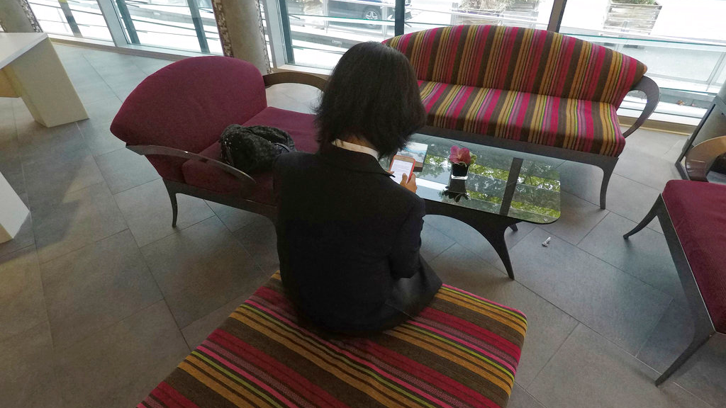 Grace Meng, the wife of missing Interpol President Meng Hongwei, who does not want her face shown, consults her mobile phone in the lobby of a hotel in Lyon, central France, where the police agency is based, on Sunday Oct. 7, 2018.