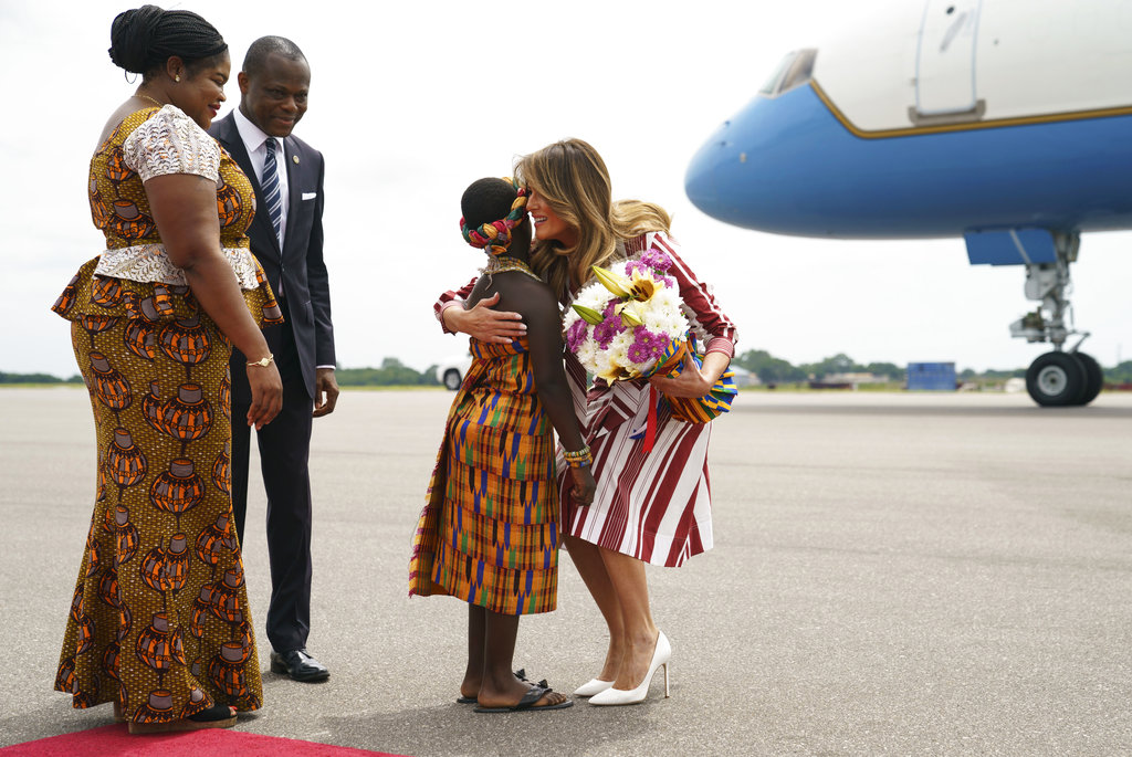 US First lady Melania Trump embraces flower girl Lillian Naa Adai Sai, 8, as she receives flowers as she arrives at Kotoka International Airport in Accra, Ghana. (AP Photo/Carolyn Kaster)