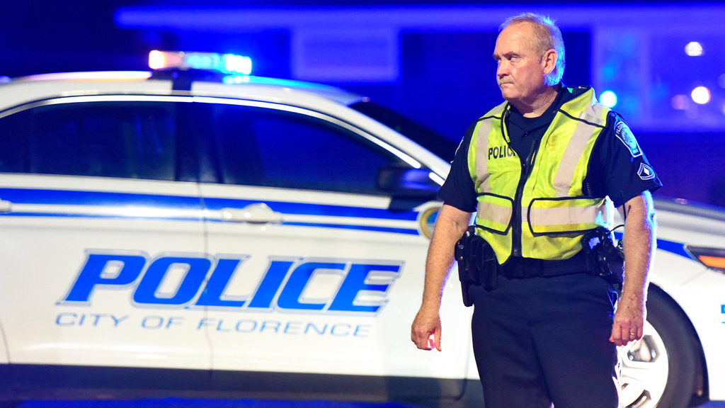 A police officer directs traffic on Hoffmeyer Road near the Vintage Place neighborhood where three deputies and two city officers were shot Wednesday, Oct. 3, 2018, in Florence, S.C. (AP Photo/Sean Rayford)