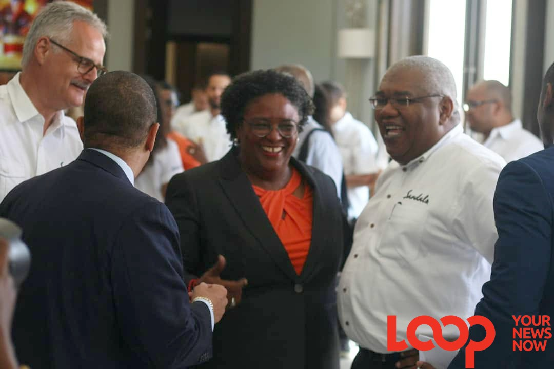 Prime Minister Mia Mottley (center) speaking with Senior VP of Sales and Marketing, Gary Sadler (right). 