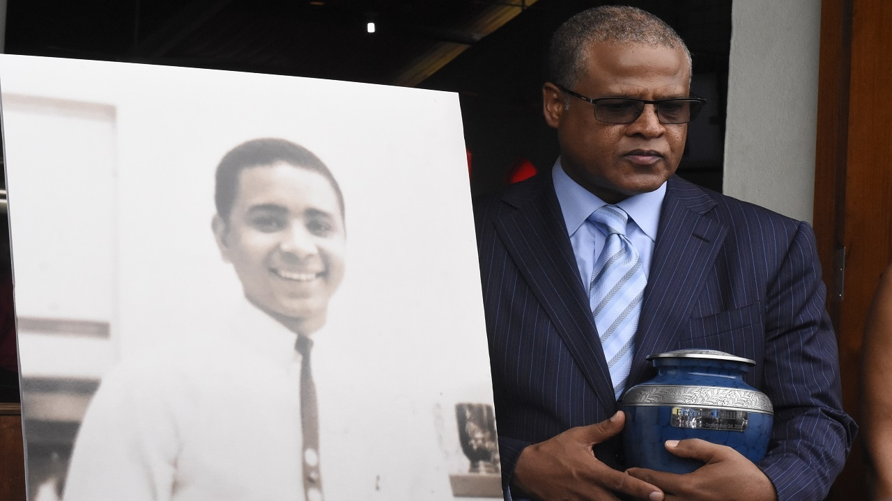 Errol Miller's younger brother, Peter Pratt, with the urn containing the ashes of his brother at the thanksgiving service for Miller in St Andrew on Saturday.