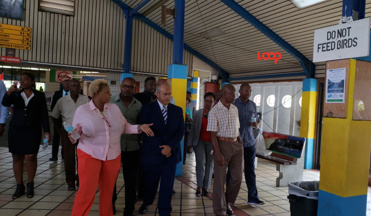 Lynda Holder (left front) speaking with the Minister of Transport Dr. William Duguid after a tour of the Transport Board and UCAL where he saw how many buses were off the road awaiting fixes.