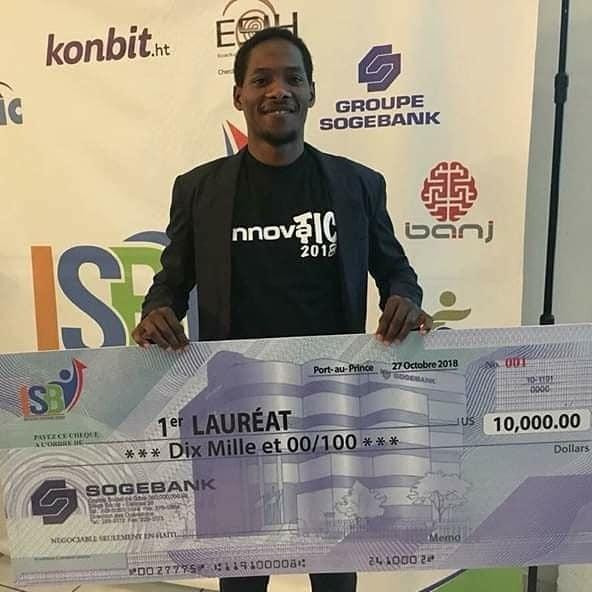 Certil Remy posant avec le chèque symbolique de $ 10000 US