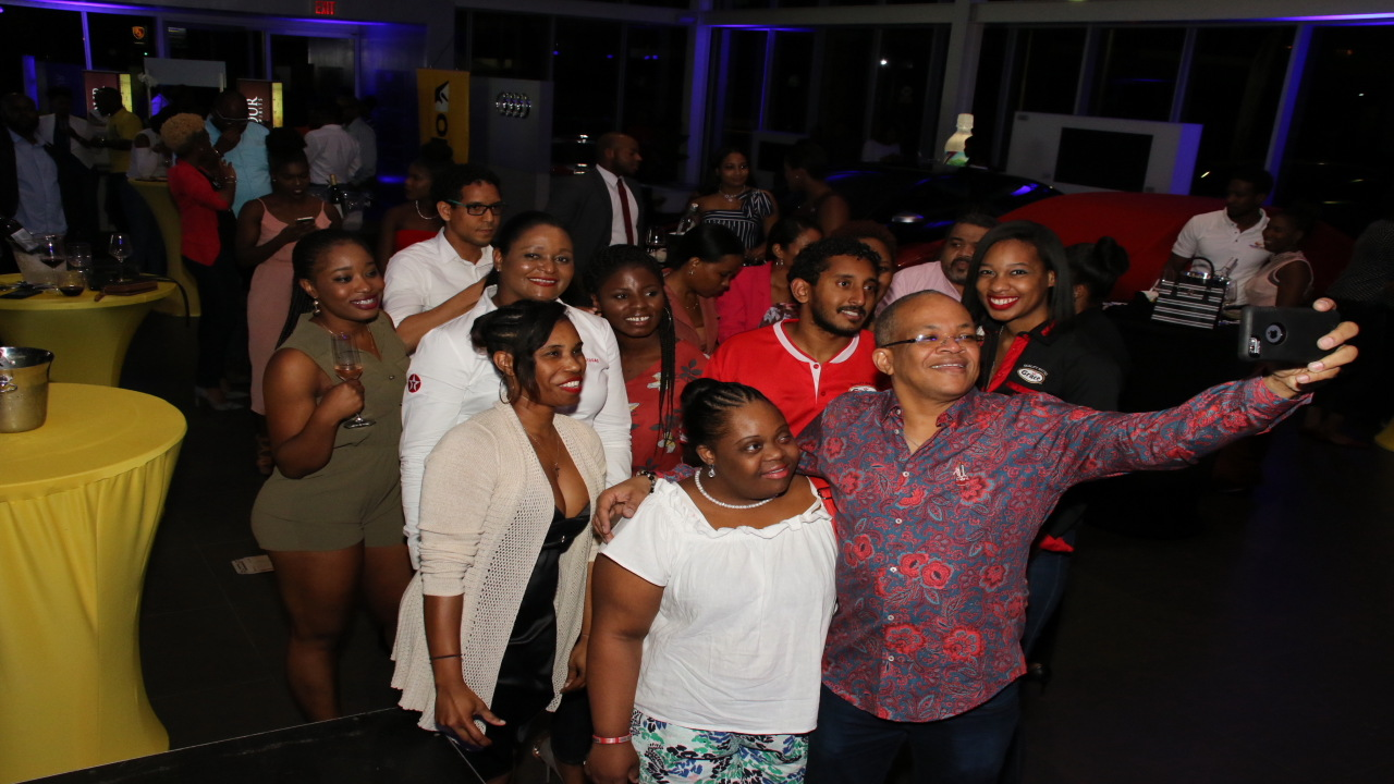 Dr Michael Abrahams, the host for the event, takes a selfie with patrons at Wine Down for Charity at the Audi Terminal on Friday. (PHOTOS: Llewellyn Wynter)