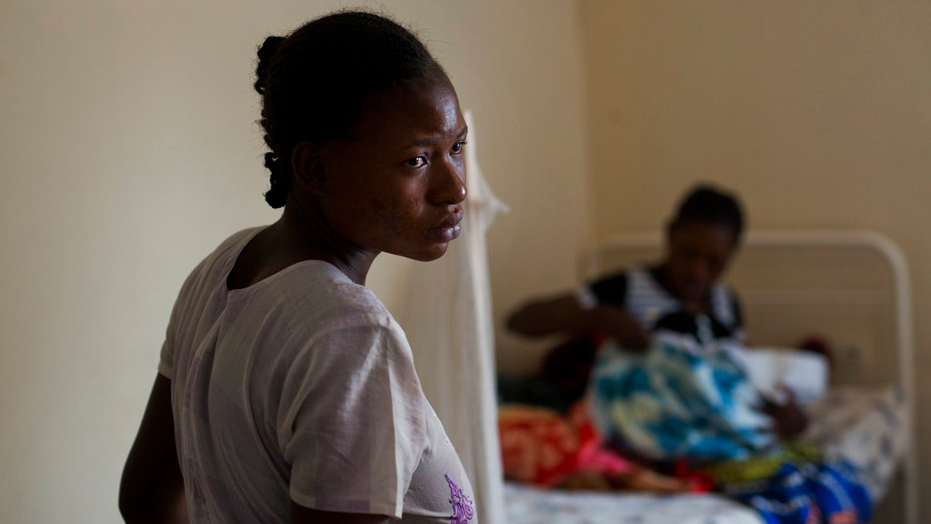 Alice Kabuya, 20, stands in the Masaidizi Health Center in Lubumbashi, Democratic Republic of the Congo on Tuesday, Aug. 14, 2018.  She gave birth to her daughter at the facility and cannot pay the $150 medical bill. Her jobless husband is trying to gather the funds so she had their daughter can be released.  (AP Photo/Jerome Delay)