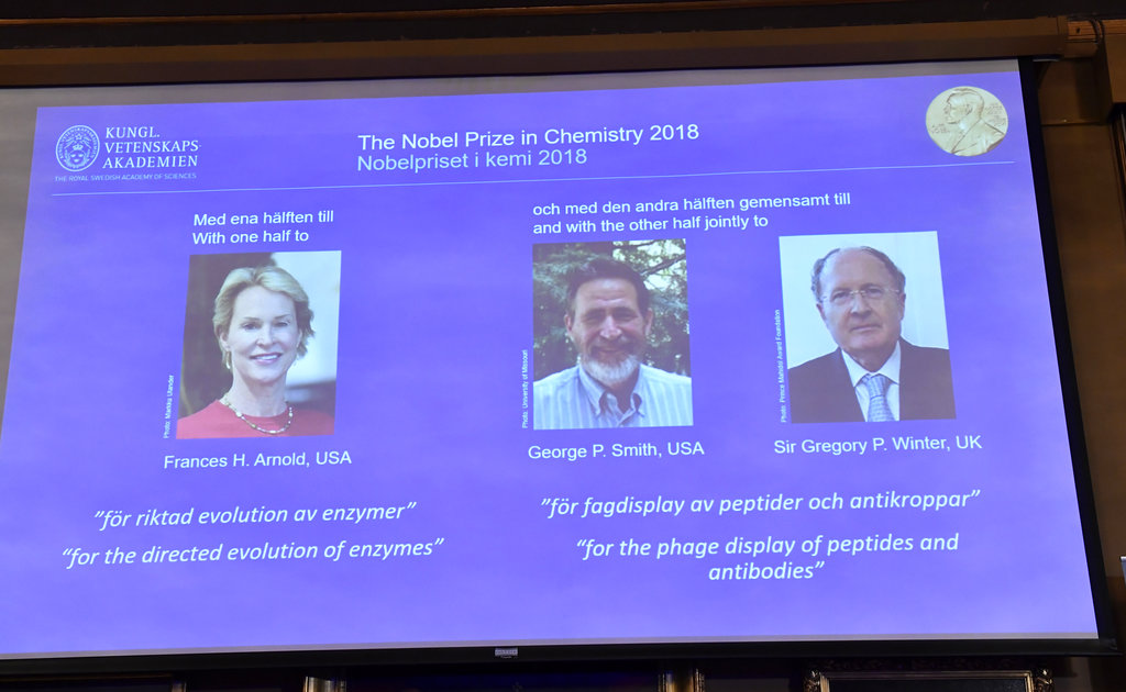The 2018 Nobel Prize laureates for Chemistry are shown on the screen from left, Frances H Arnold of the US, George P Smith of the US, and Gregory P Winter of Britain, during the announcement at the Royal Swedish Academy of Sciences in Stockholm. (Jonas Ekstromer/TT via AP)