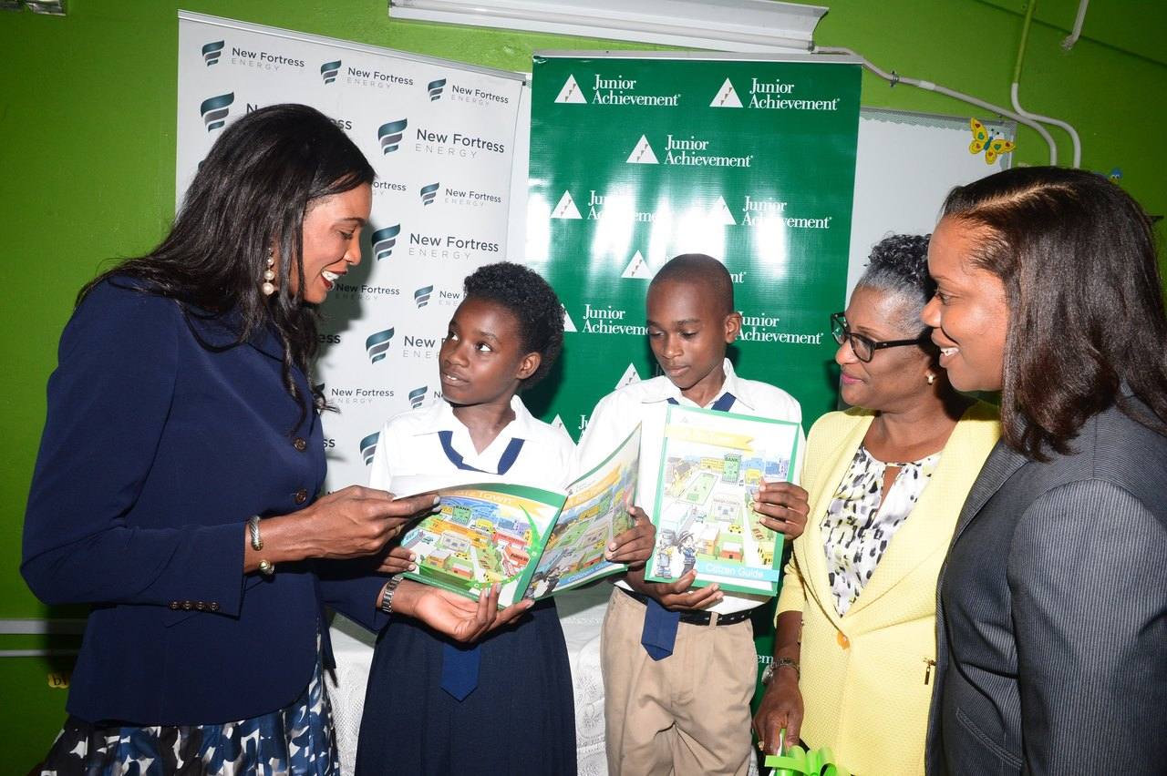 Race Course Primary students, Kareen DeSouza and Dorian Reid, took Verona Carter, VP Public Affairs, New Fortress Energy, through the JA BizTown workbook during a recent visit to the school. Meanwhile, looking on are Monica Smilie, Principal, Race Course Primary and Alphie Mullings-Aiken, President, Junior Achievement Jamaica.