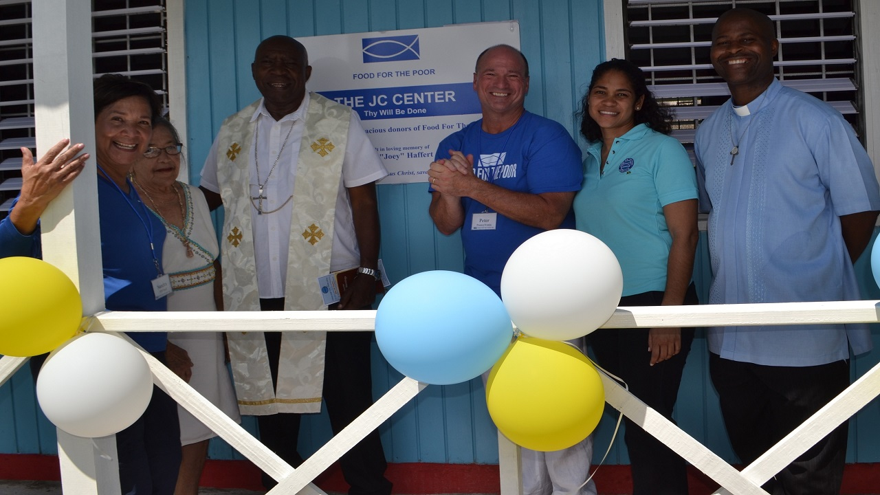 Sandra Caskey (left), Senior Field Representative at Food For The Poor Inc.; Dorothy Harker, eldest active member of the Sts. Philip and James Roman Catholic Church; the Most Rev. Burchell McPherson, Roman Catholic Bishop of Montego Bay; Peter Anninos, donor; Catherine Goodall, Director of Projects Development of  Food For The Poor- Jamaica and Rev. Fr. Carl F. Clarke, pastor at the church were all smiles during the unveiling of the JC Centre sign just moments following the ribbon-cutting .