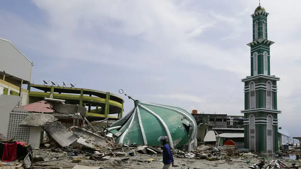 A man walks past the remains of a mosque after it was destroyed in the massive earthquake and tsunami that hit Palu, Central Sulawesi, Indonesia Thursday, Oct. 4, 2018. (AP Photo/Aaron Favila)