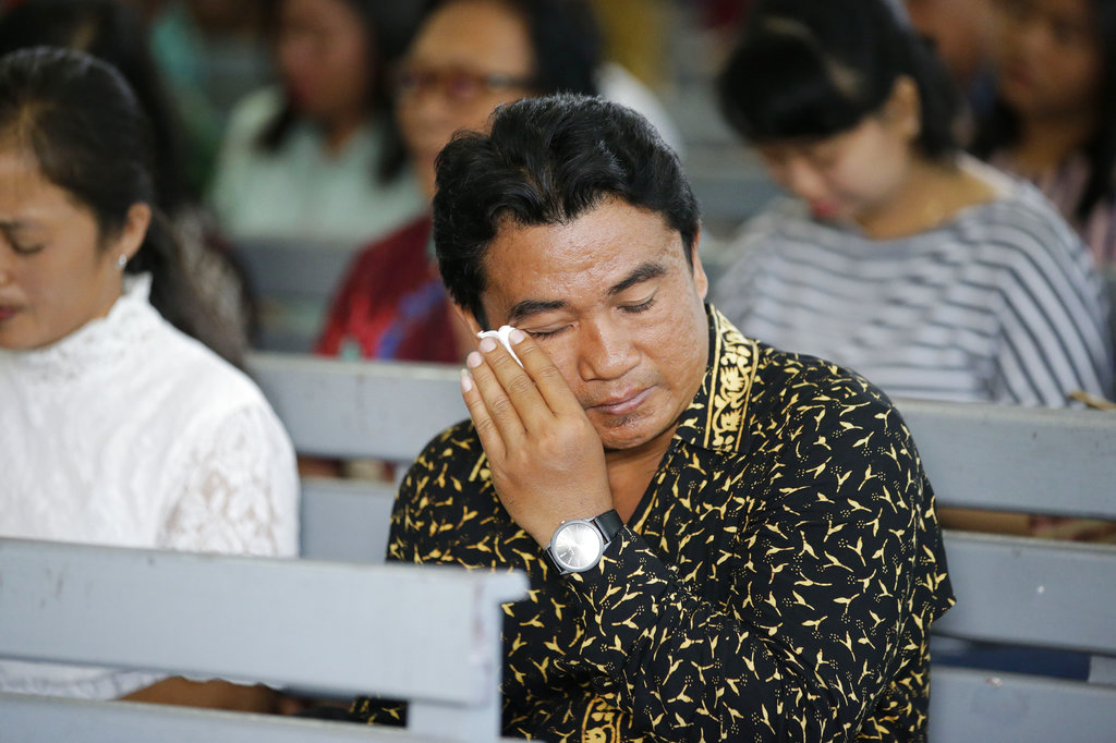 A Christian wipes tears from his eyes as he attends church at the earthquake and tsunami-hit town of Palu, Central Sulawesi, Indonesia. (AP Photo/Aaron Favila)