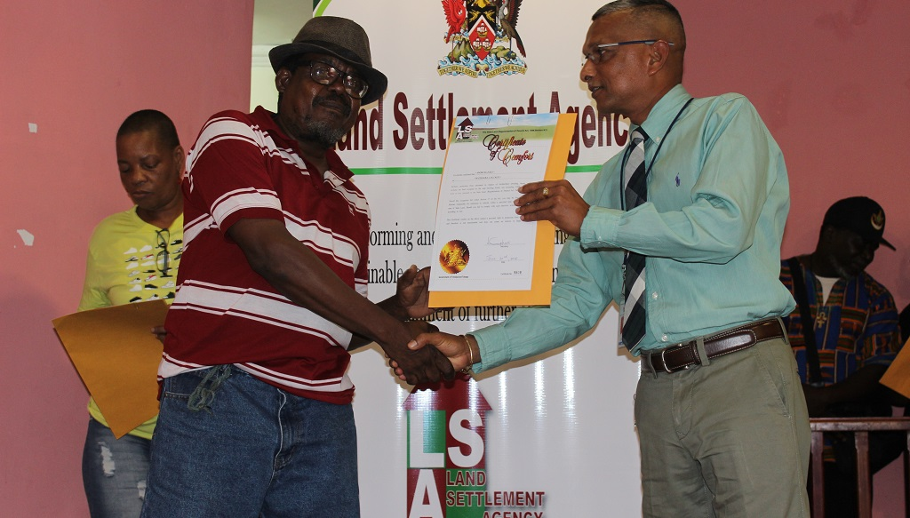 Photo: A resident of Diego Martin receives his Certificate of Comfort in a distribution ceremony in October 2018.