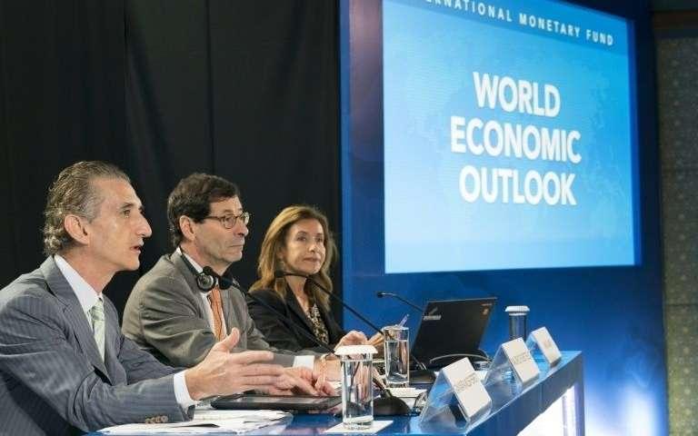Photo remise par le FMI de la conférence de presse à Bali le 9 octobre 2018 avec Maurice Obstfeld (centre), économiste en chef du Fonds, du directeur adjoint Gian Maria Milesi-Ferretti (gauche) et de la responsable de la communication Wafa Amr (droite)