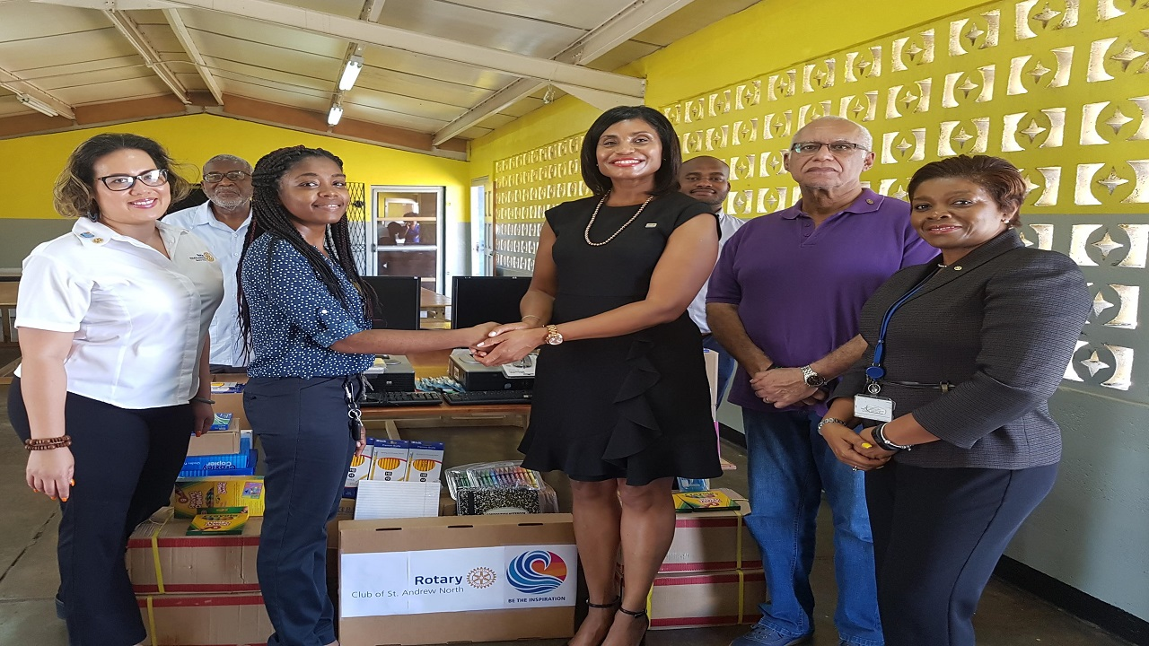 Director of Service Projects for the Rotary Club of St. Andrew North Kecia Taylor (third right) hands over school supplies and computers to Tamara Rowe from Chetolah/Mel Nathan Education Centre.  Looking on (from left) are: Club President Lori Chuck; Past President Joscelyn Jolly; Immediate Past President Andrew Jackson; Past President Michael Martin and President Elect Annmarie Curtis.