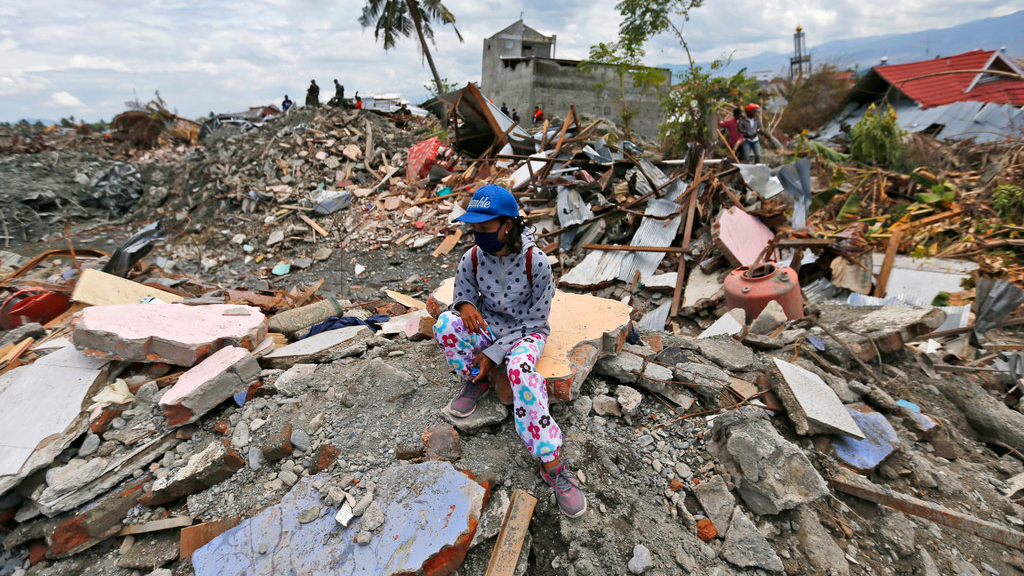 A woman sits on a pile of rubble in an area devastated by an earthquake in the Balaroa neighborhood of Palu, Central Sulawesi, Indonesia, Monday, Oct. 8, 2018.