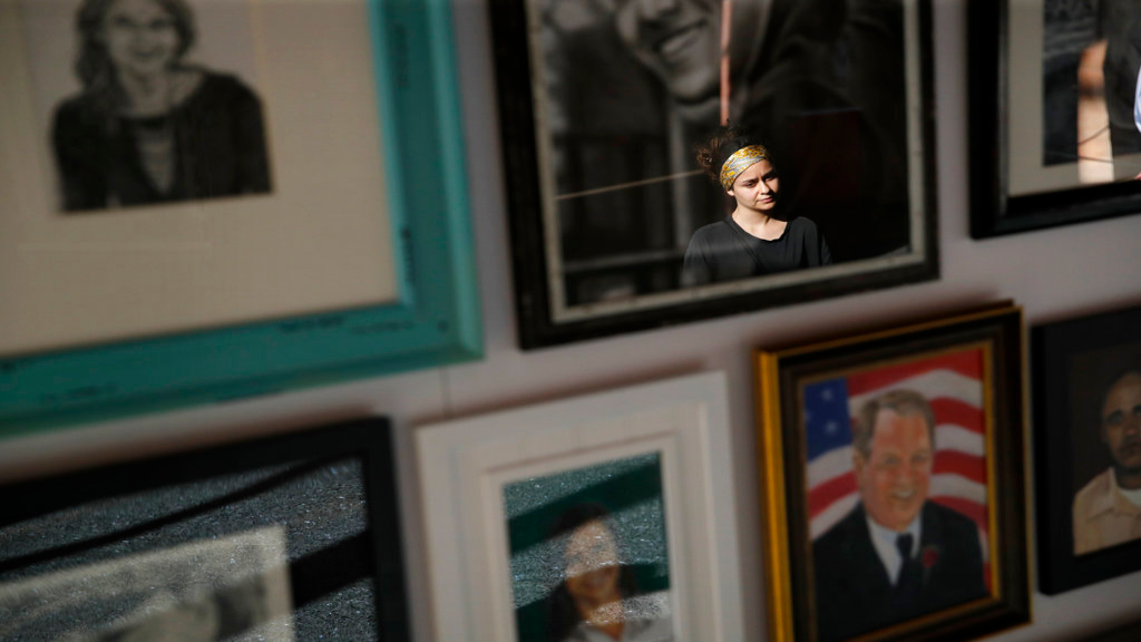 n this Sept. 25, 2018, photo, a woman looks at painted portraits of victims of the Oct. 1, 2017, mass shooting in Las Vegas on display at the Clark County Government Center in Las Vegas. (AP Photo/John Locher)