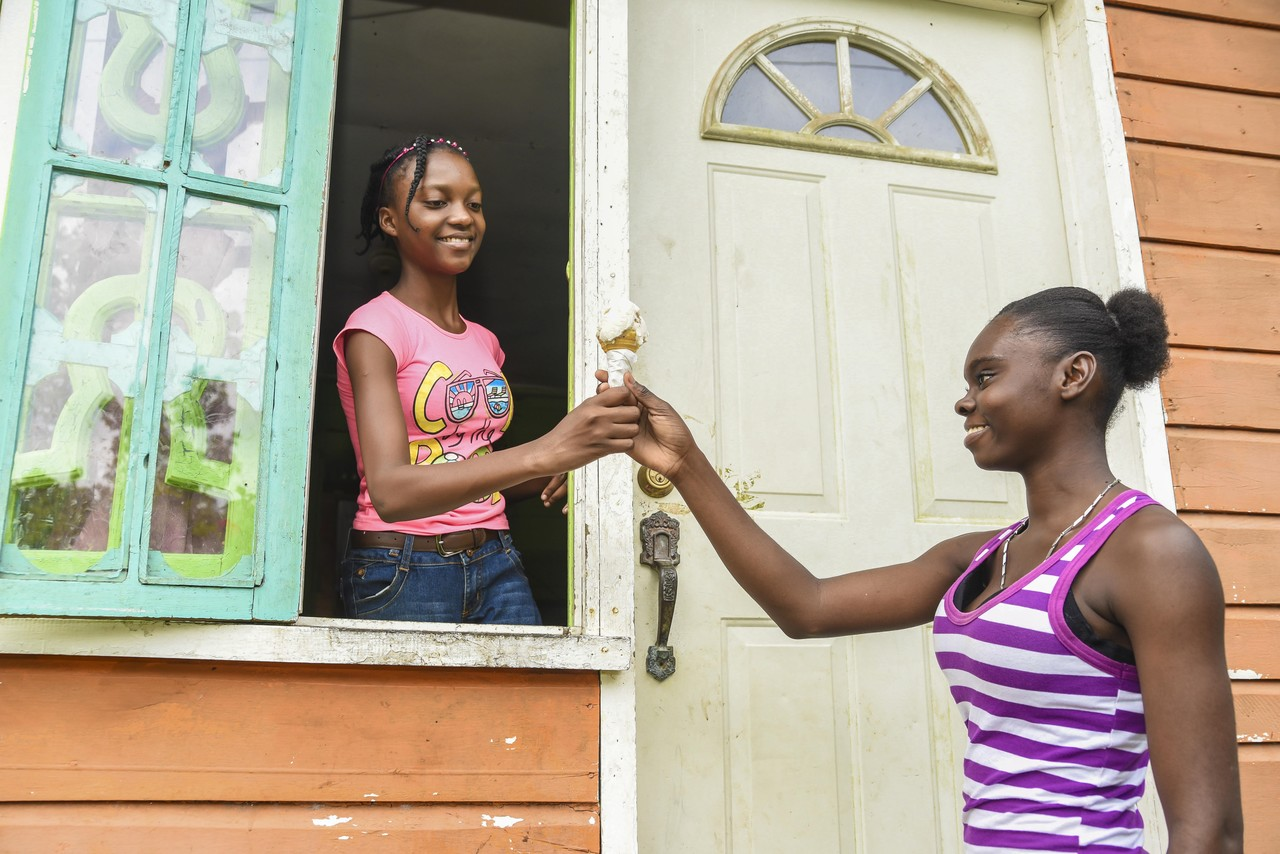 Young entrepreneur, Ryesha Gordon (left), sells ice-cream to a customer at her home in New Works, Westmoreland.