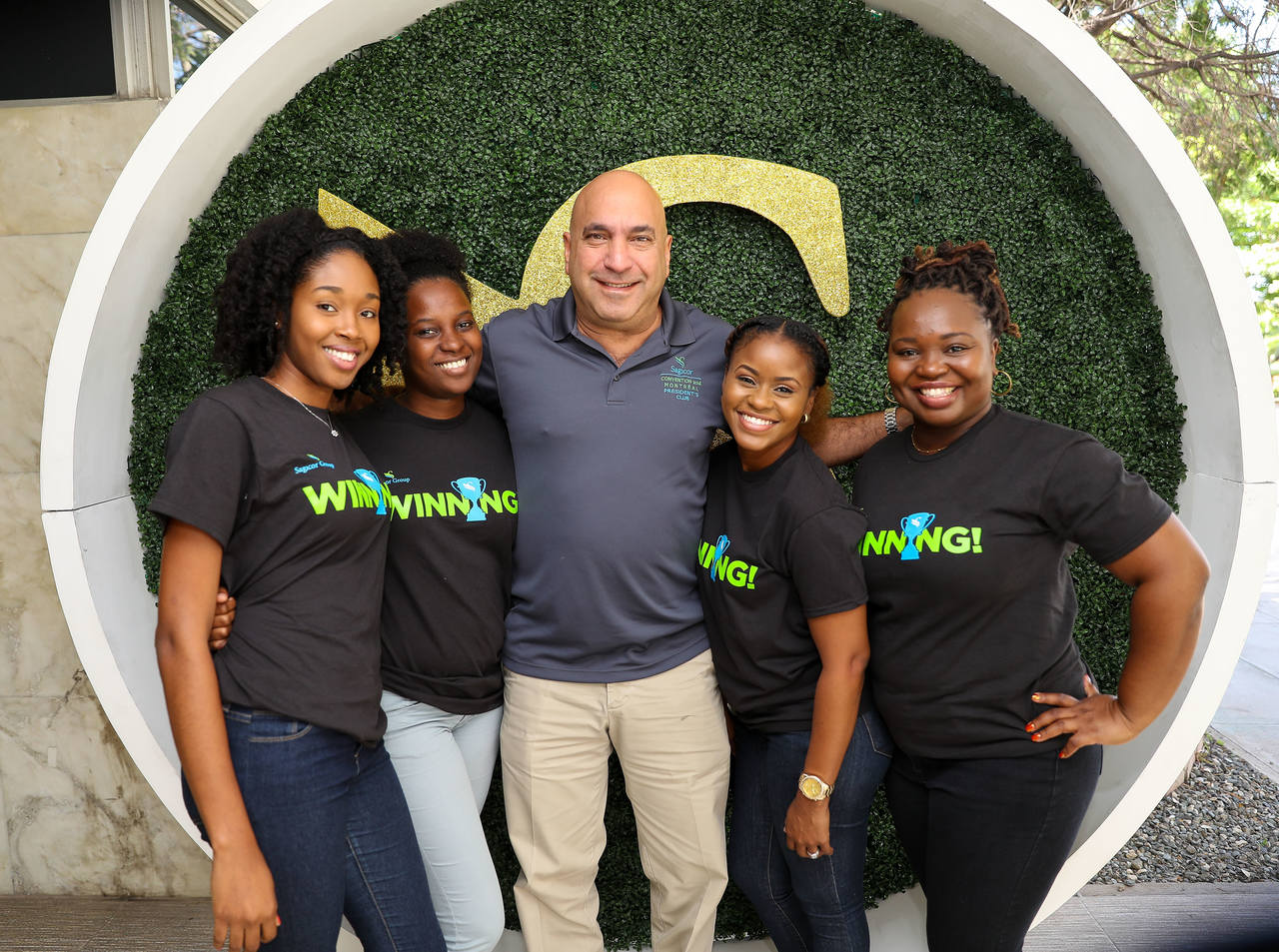 Sagicor Group Jamaica President and CEO Christopher Zacca poses for a photo op with members of the Sagicor tram.