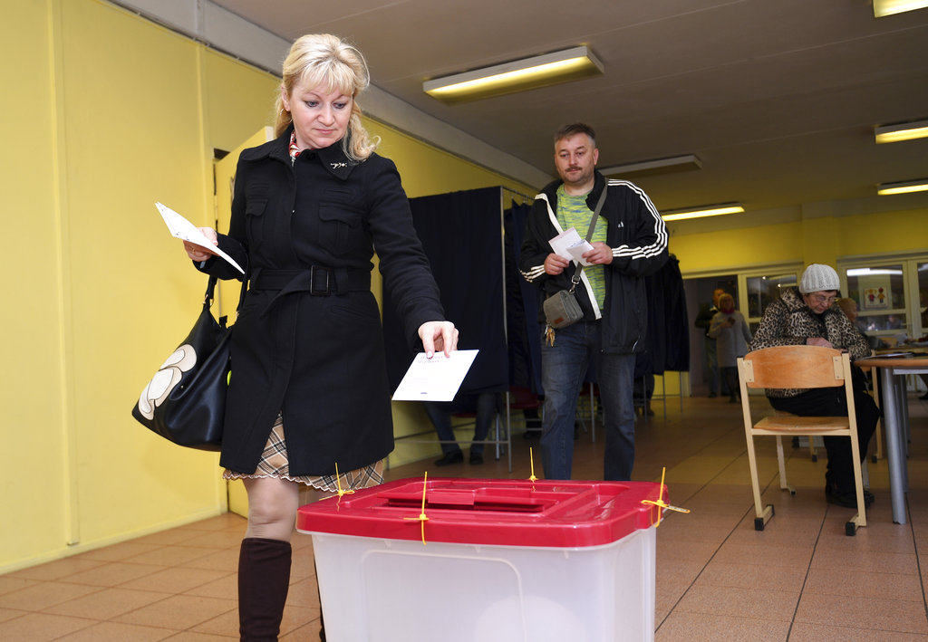 A Latvian woman casts her ballot papers at a polling station in Riga, Latvia. (AP Photo/Roman Koksarov)