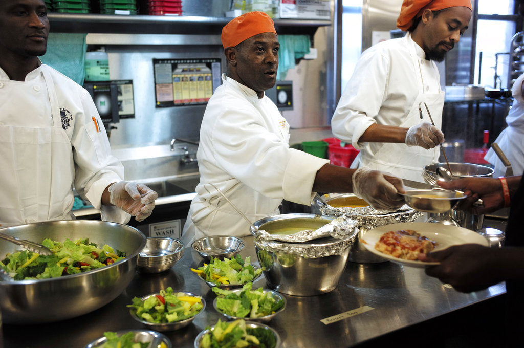 Phillip Oliver, of New Bedford, Massachusetts, center, in recovery from opioid addiction, helps serve a meal in a culinary training program at the New England Center for Arts and Technology, in Boston. (AP Photo/Steven Senne)
