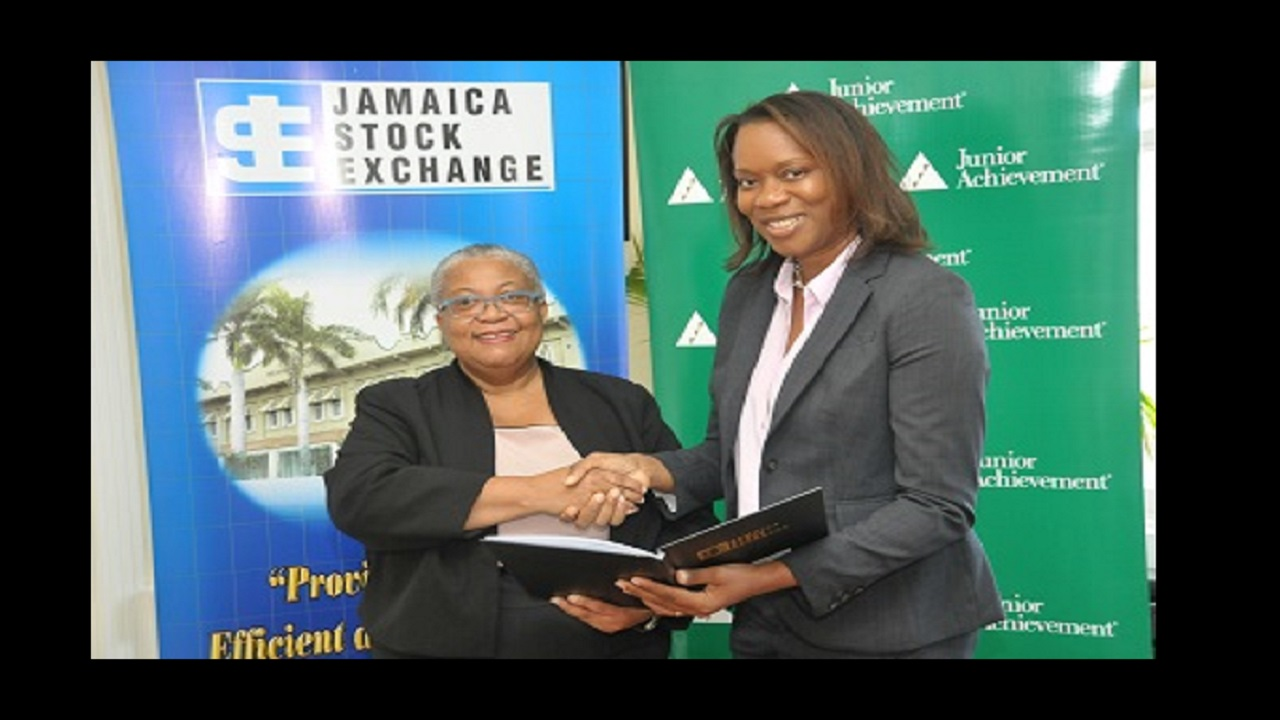 JSE Managing Director Marlene Street Forrest (left) and Alphie Mullings-Aiken, President of Junior Achievement Jamaica following the signing of an MoU between the two entities.