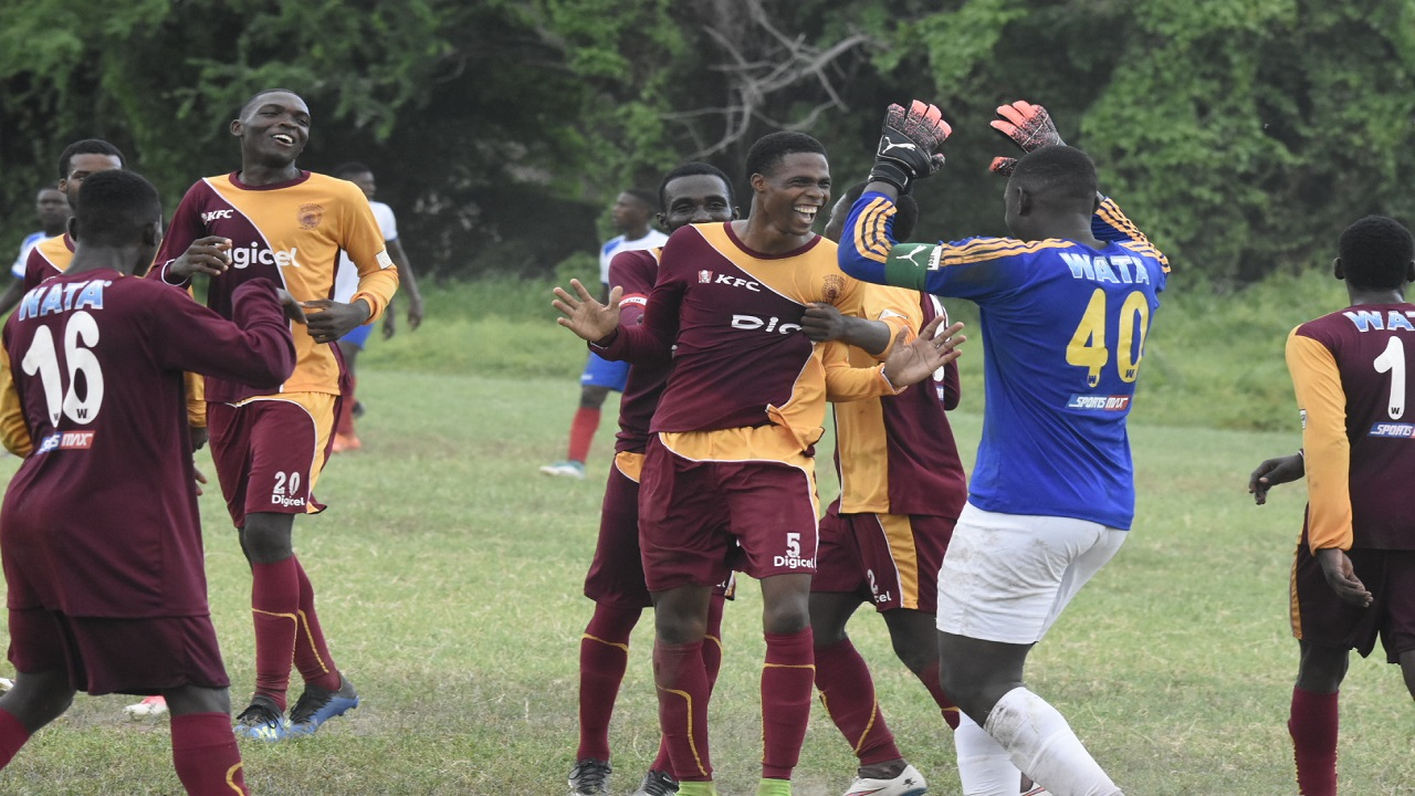 Wolmer's goalkeeper Tajay Griffiths celebrates a goal with teammates during their Group G top-of-the-table return-leg fixture against Holy Trinity High at Bell Chung Oval on Friday, September 28, 2018. Wolmer's won 2-1. (PHOTOS: Marlon Reid).