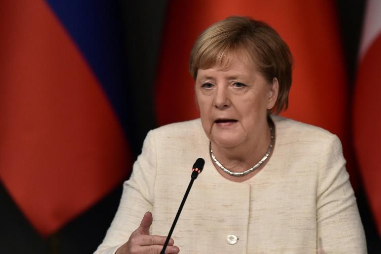 La chancelière allemand Angela Merkel regarde sa montre en attendant l'arrivée à la chancellerie à Berlin de dirigeants africains pour une conférence sur le commerce, l'aide internationale et la diplomatie, le 30 octobre 2018