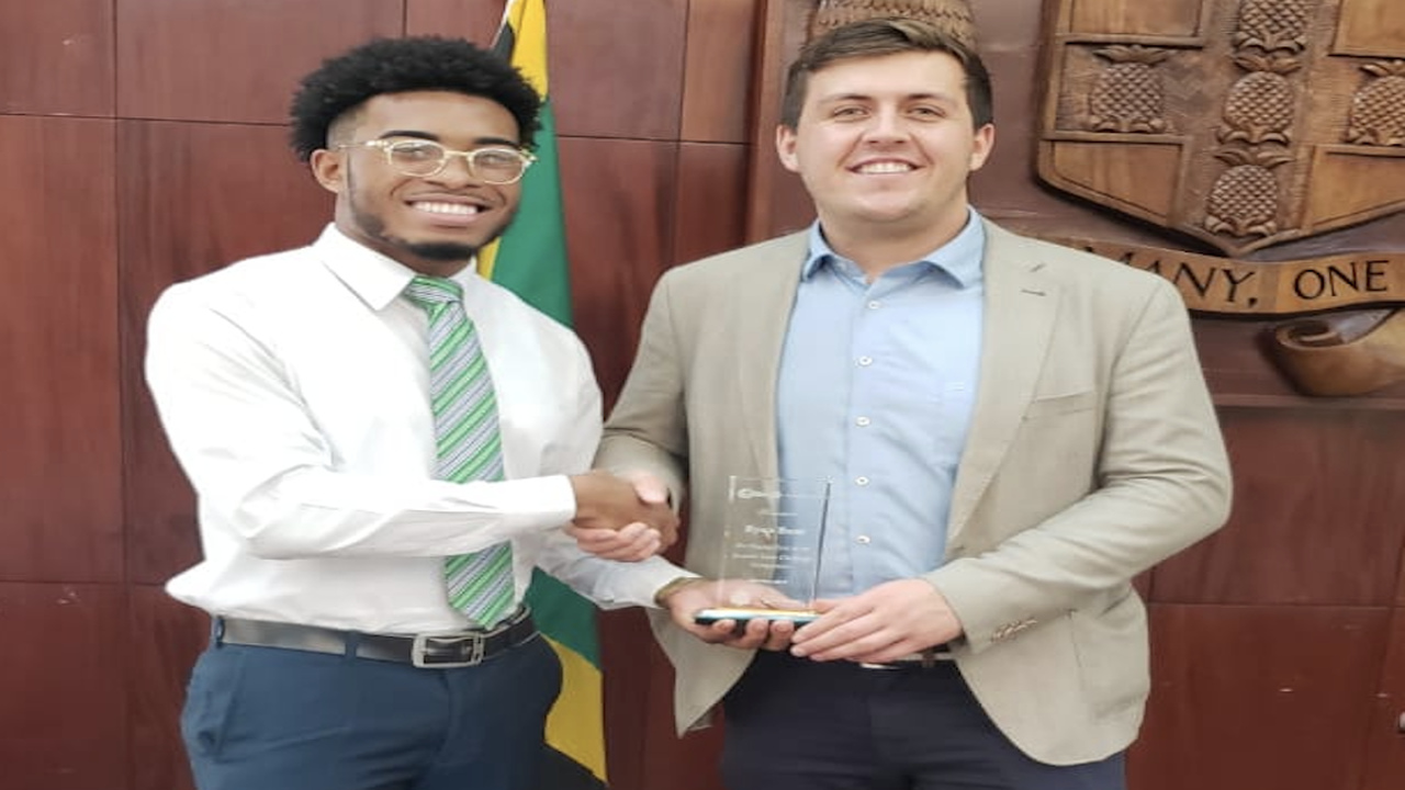 Jamaica Solar Challenge winner Ryan Bent receives his award from Solar Head of State Director James Ellsmoor.