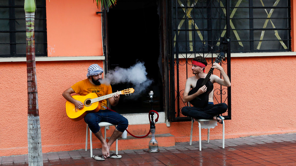 Two young men smoke and play their guitars as they wait for the landfall of Hurricane Willa in Mazatlan, Mexico, Tuesday, Oct. 23, 2018. Emergency officials said they evacuated more than 4,250 people in coastal towns and set up 58 shelters ahead of the dangerous Category 3 storm. (AP Photo/Marco Ugarte)