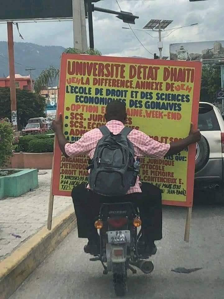 Un homme transporte une affiche d'une annexe de l'Ecole de droit et sciences économiques des Gonaives