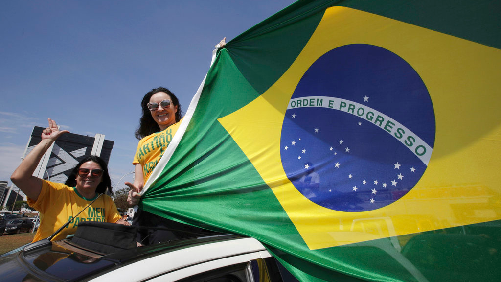 Demonstrators show the flag of Brazil during a race in support of Jair Bolsonaro, presidential candidate for the National Social Liberal Party, in the center of Brasilia, Brazil, Saturday, Oct. 6, 2018. Brazil will hold general elections on Oct. 7. (AP Photo/Eraldo Peres)