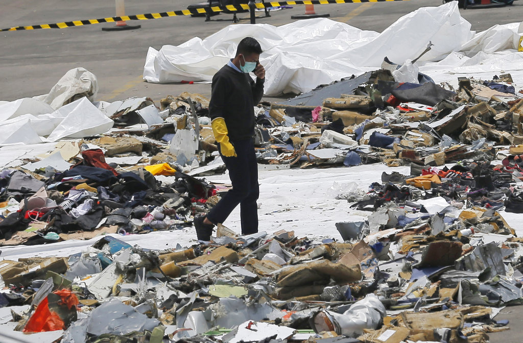 An investigator walks amid debris of Lion Air Flight 610 retrieved from the waters off Tanjung Priok in Jakarta, Indonesia, Wednesday, Oct. 31, 2018. A massive search effort identified the possible seabed location of the crashed Lion Air jet, Indonesia's military chief said Wednesday, as experts carried out the grim task of identifying dozens of body parts recovered from a 15-nautical-mile-wide search area. (AP Photo/Tatan Syuflana)