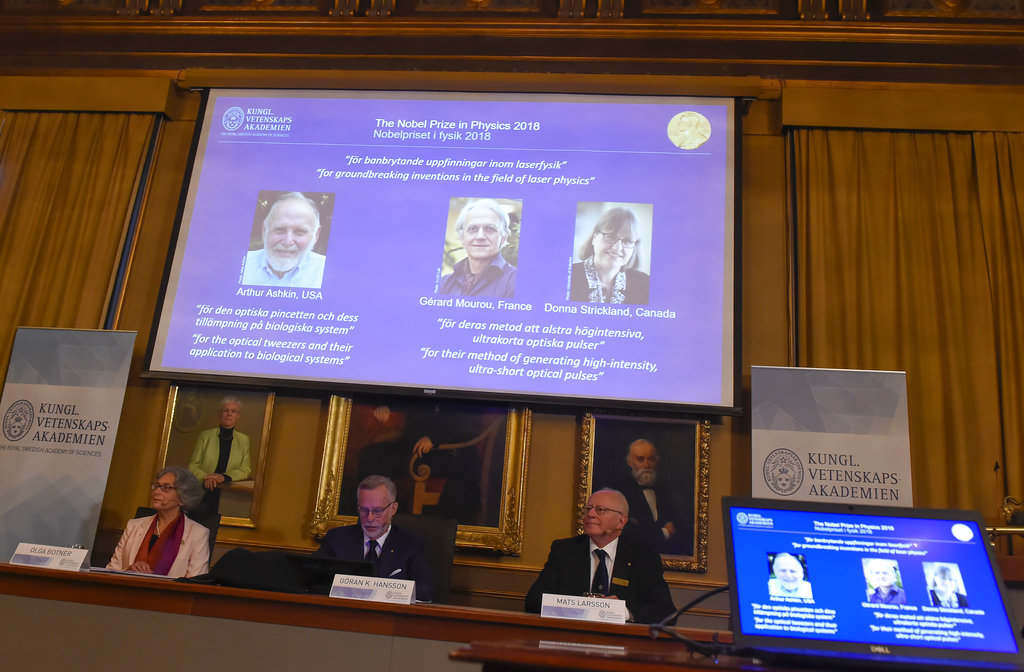 The Nobel Prize laureates for physics 2018 shown on the screen from left, Arthur Ashkin of the United States, Gerard Mourou of France and Donna Strickland of Canada during the announcement at the Royal Swedish Academy of Sciences in Stockholm, Sweden. (Hanna Franzen/TT via AP)