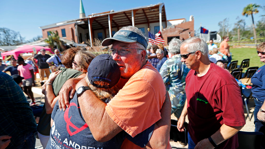 Jerry Register a congregation member of St. Andrew United Methodist Church hugs a fellow church member during Sunday service outside the damaged church in the aftermath of Hurricane Michael in Panama City Fla. Sunday Oct. 14 2018. (AP