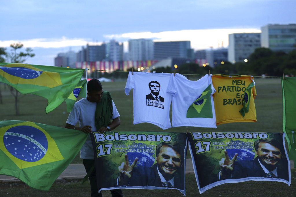 A man sells T-shirts and flags with the image of presidential frontrunner Jair Bolsonaro of the Social Liberal Party, in front of the headquarters of the national congress, in Brasilia, Brazil. (AP Photo / Eraldo Peres)
