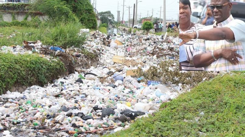 File photo of garbage in a gully along Marcus Garvey Drive following a flooding episode there. (INSET: Desmond McKenzie)