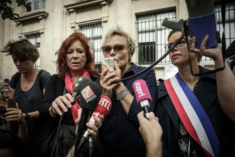 """Des manifestants portent une banderole """"Femmes battues Justice complice Assez!"""" lors d'un rassemblement organisé par l'actrice Muriel Robin contre les violences faites aux femmes, le 6 octobre 2018 à Paris"""