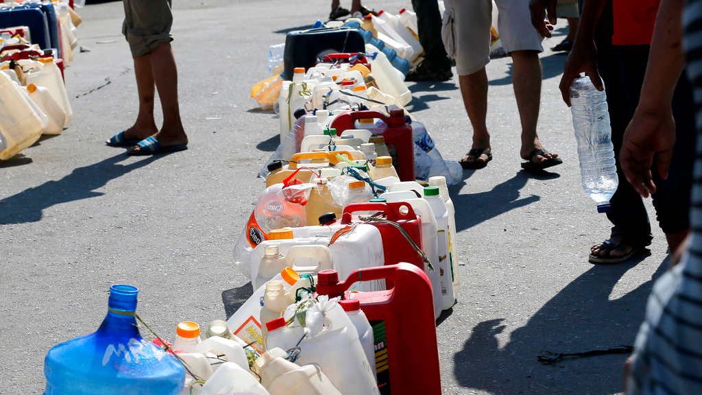 People queue for gasoline following a massive earthquake and tsunami at a gas station in Palu, Central Sulawesi, Indonesia, Monday, Oct. 1, 2018. (AP Photo/Tatan Syuflana)