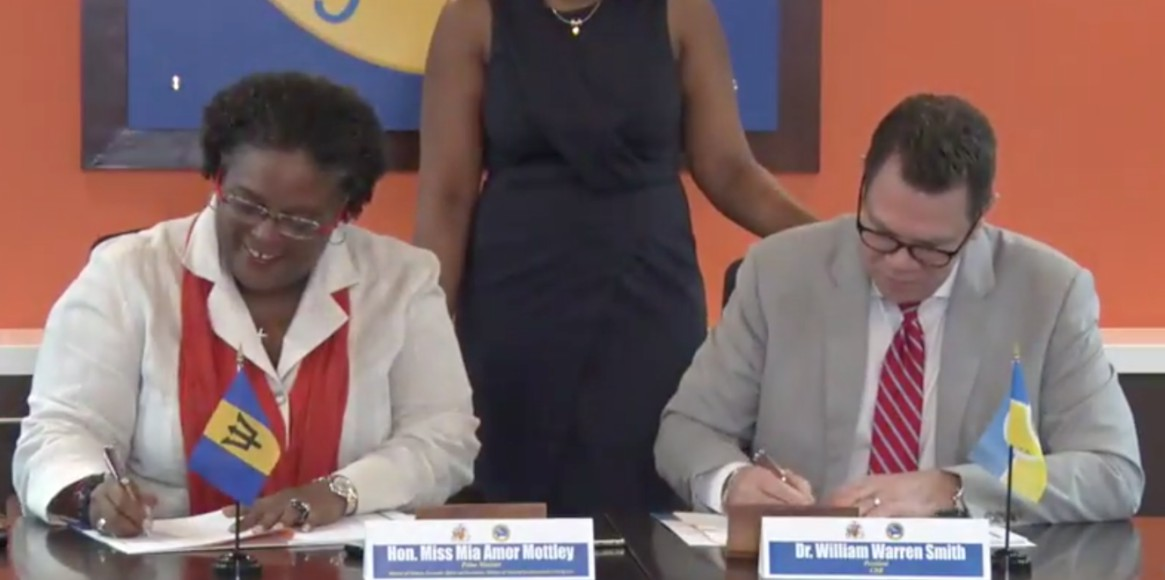 Prime Minister Mia Mottley and CDB President, Dr. William Warren Smith signing off on the loan agreement.