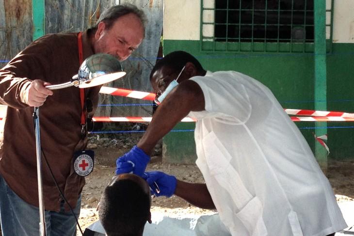 Illustration d'un médecin du CICR qui assiste un médecin de la Direction de l'administration pénitentiaire lors de soins dentaires dispensés aux détenus à la prison civile de Jacmel – Crédit Photo : www.icrc.org