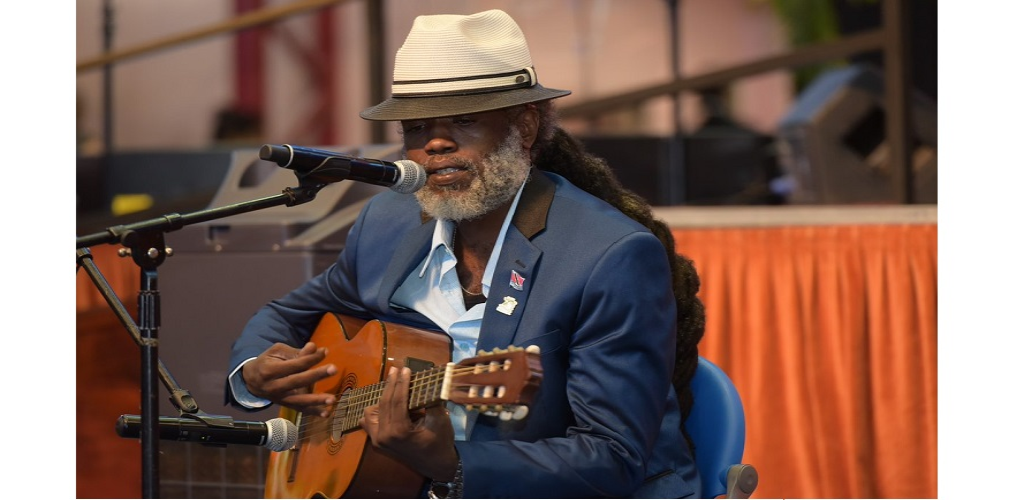 """Sharlan Bailey accepted the honorary degree on his father's behalf and performed his father's 1982 classic, """"One Love"""" at the graduation ceremony on Saturday. (Photo courtesy: UWI St. Augustine)"""