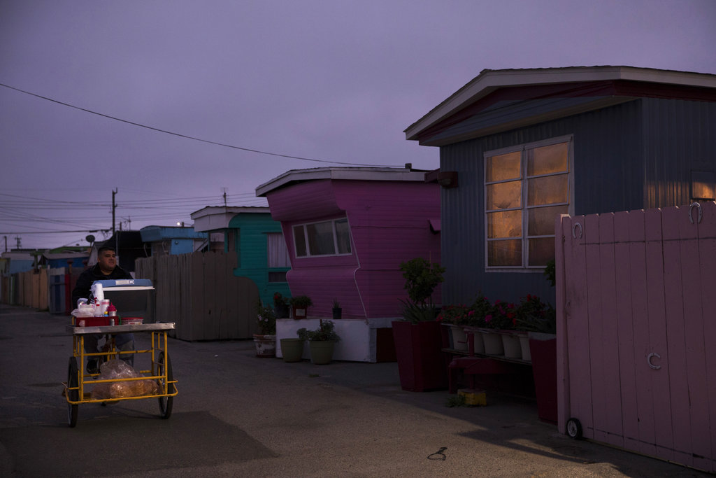 A food vendor passes through a mobile home park, where the majority of tenants are farm workers, in Salinas, California. (AP Photo/Jae C. Hong)