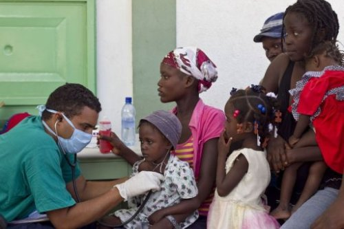 Illustration d'un médecin cubain prodiguant des soins a un patient / enfant haïtien - Crédit Photo : HPN