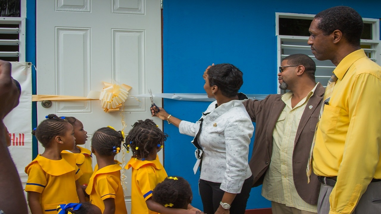 From left  Sharon Williams, Kiwanis Lt. Gov 2017-2018 cuts the ribbon to declare the new kitchen open, supported by Leighton James, President of Kiwanis Club of Stony Hill and George Lynch, Pastor of the Wesleyan Holiness Church, Golden Spring, St. Andrew, with some students looking on.