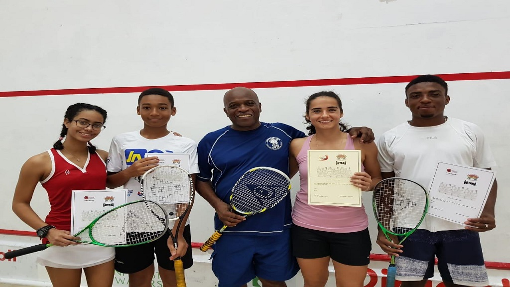 Tahjia Lumley (right) former junior national squash champion, displays his certification after he successfully completed Level 1 & 2 England Squash Coaching training courses. Sharing in the moment are (from left) Guyanese junior players Sarah Lewis and Samuel Ince-Carvalhal, Guyana's national squash coach, Carl Ince  and Guyanese professional squash player and former Caribbean Champion, Nicolette Fernandes.
